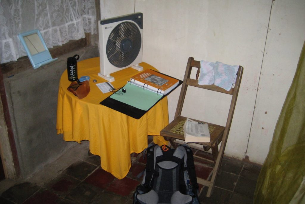 The view of my desk in Nicaragua as a Peace Corps volunteer. You can see concrete stone block walls, a small table with a cover over it, a fan, a foldout chair, and the edges of a mosquito net. A simple existence. Lifestyle creep started from a low level for me!