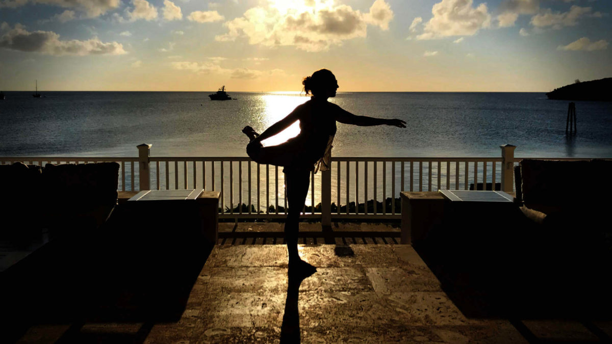 A healthy work-life balance with your email takes practice and effort. Jenni poses, balanced, on a patio in Eleuthera, Bahamas.