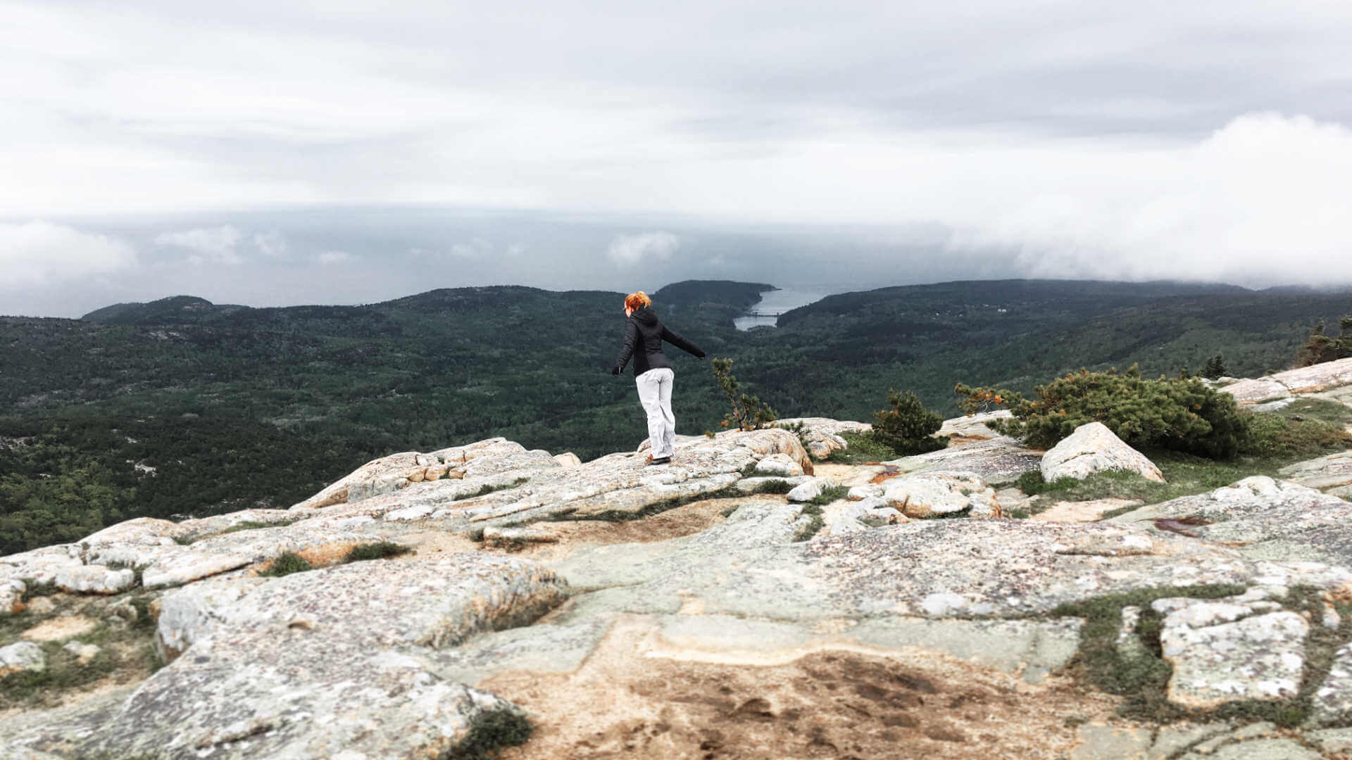 Jenni staring down over a peak in Acadia National Park, balancing near the edge - keeping things just right like with work-life balance.